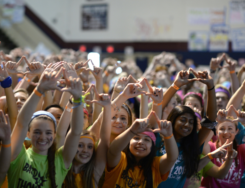 Several young people in a school gymnasium hold their arms in the air, making a diamond formation using the thumb and forefinger of each hand.