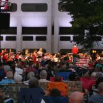 """A crowd is in the foreground, seated on lawn chairs and blankets, with an orchestra in the background. The backdrop is Hershey Medical Center's signature """"Crescent."""""""