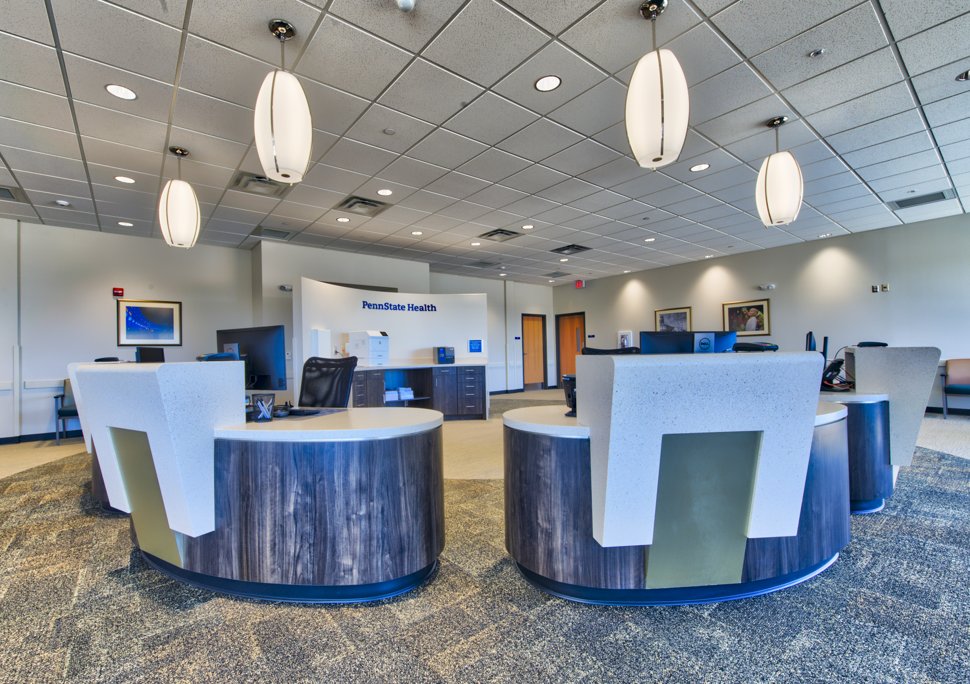 Inside the new Penn State Medical Group site in Mechanicsburg, four white pendulum lights hang down over the registration area, made up of blue desks with elevated white counters in a semicircle in the center of a room, which has the Penn State Health logo on the rear wall.