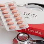 """A stethoscope lays on a white table. On top of it is a white and read box labeled """"STATIN"""" and a pill pack with 14 brown caplets."""