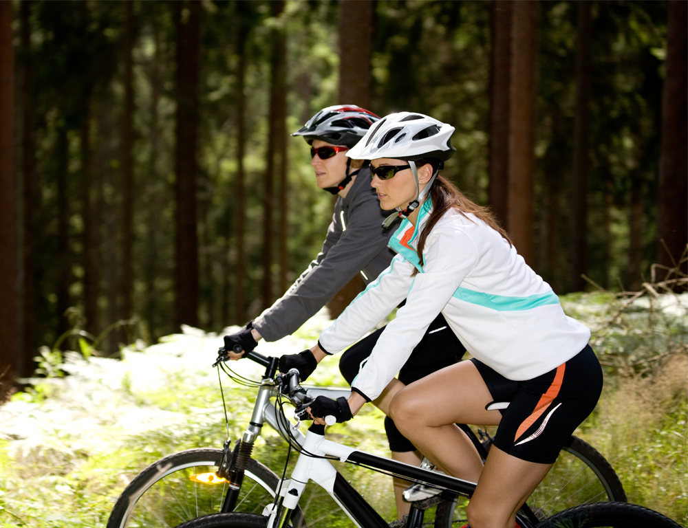 Side view of two women on bikes, wearing biking gear. Some grass and a row of tall trees are in the background.