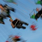 A partially sideways view of riders on an amusement park swing ride, blurry to depict motion.