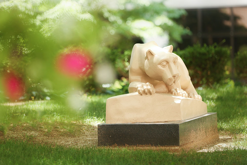 The Penn State Nittany Lion statue is seen in Penn State College of Medicine's outdoor courtyard. The statue is seen at the right of the photo in focus, framed by trees and pink flowers to the left and above and grass below.