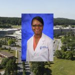 Annyella Douglas poses in a white coat against a blue backdrop; the image is superimposed over an aerial view of the Milton S. Hershey Medical Center-Penn State College of Medicine campus.