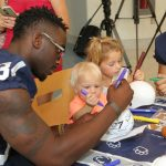 A Penn State football player sits at a table with two small children. The child in the foreground is drawing on a white mini-football helmet with a marker, along with the player.