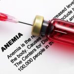 "A closeup of a syringe, the needle of which is penetrating the top of a small red bottle. The backdrop is a sheet of paper containing the word ""Anemia"" and an extensive description of the condition. Only some of the words are readable."