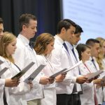 Approximately eight people wearing white doctor coats stand in a row and look down at a paper off of which they are reading in unison.