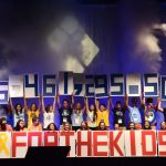 "Several people stand on a stage and hold up numbers comprising the figure $6,461,295.50. In front of them are large red letters reading ""FOR THE KIDS."""