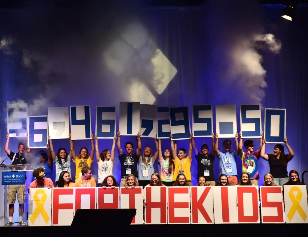 Several people stand on a stage and hold up numbers comprising the figure $6,461,295.50. In front of them are large red letters reading