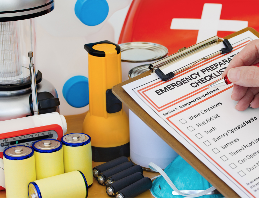 A hand holds a pen above a clipboard bearing a sheet reading Emergency Preparation Checklist. Items such as batteries, a flashlight and a radio are in the background.