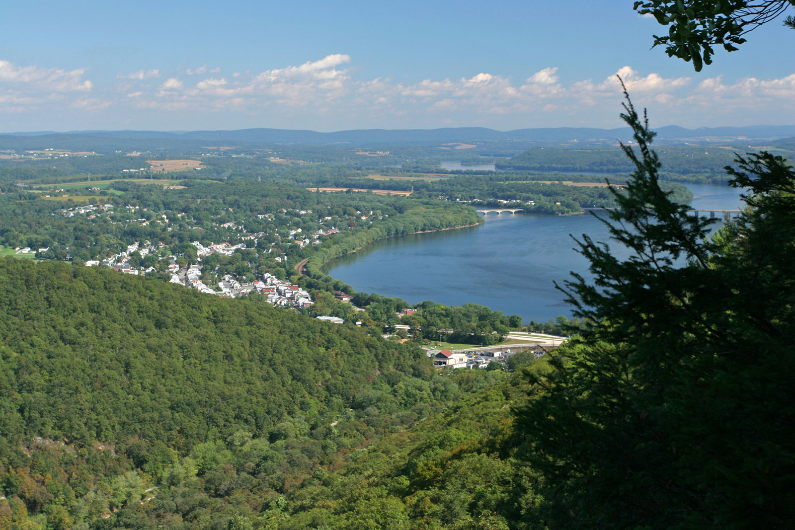 The image shows a landscape scene in the Appalachian region of Pennsylvania overlooking a quaint town dotted with white houses. A river cuts into the landscape below mountain ridge that is covered in green trees. A railroad track runs along the river. In the distance another mountain ridge stands below a blue sky with white clouds. The scene if framed to the right by out of focus pine trees in the foreground.