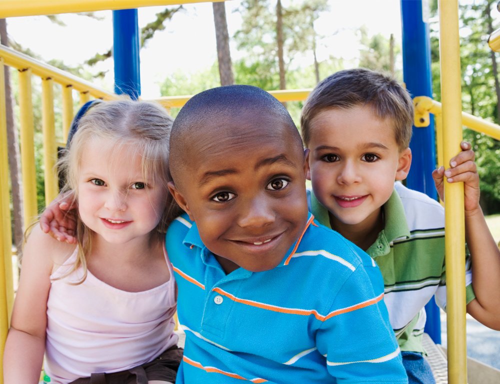 Three young children pose for a photo while sitting on a blue and yellow piece of playground equipment. A wooded area and a sunny sky are in the background.