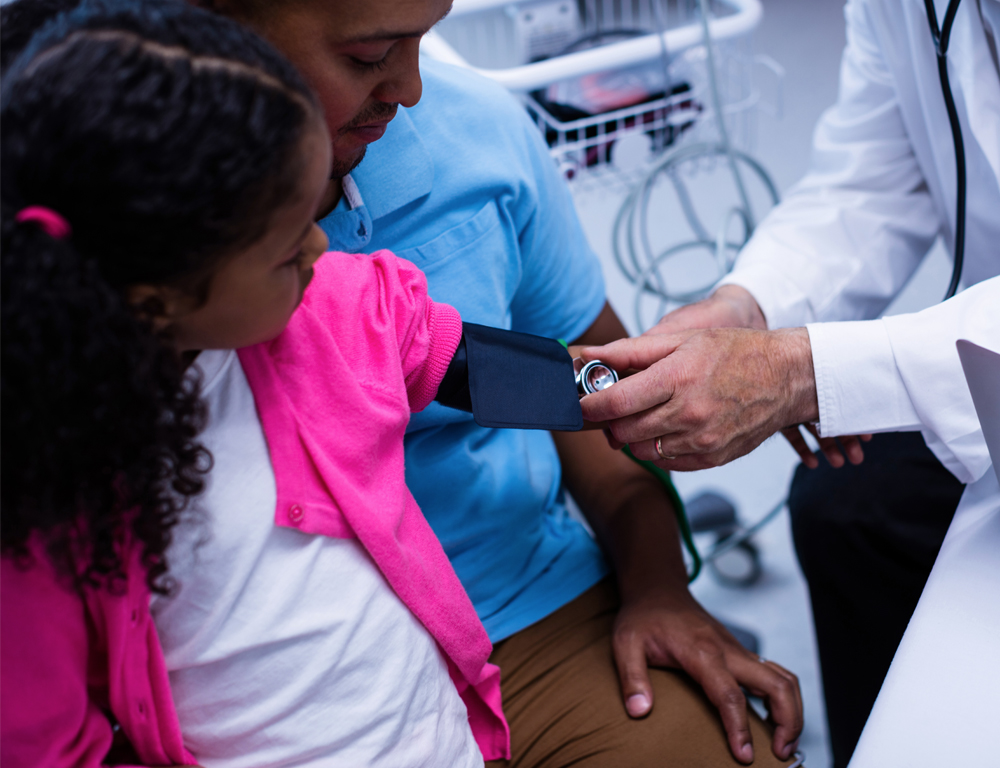 A young girl sits on her dad™s lap while a physician (at right) takes her blood pressure from her left arm.