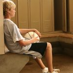 A young boy sits on a concrete bench in a locker room, surrounded by lockers. He holds a basketball in his lap and leans back against a locker, his eyes closed.