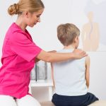 In a clinical exam room, a woman sits beside a young boy on an exam table. Her hands are on his shoulders and she appears to be looking at the boy™s spine.