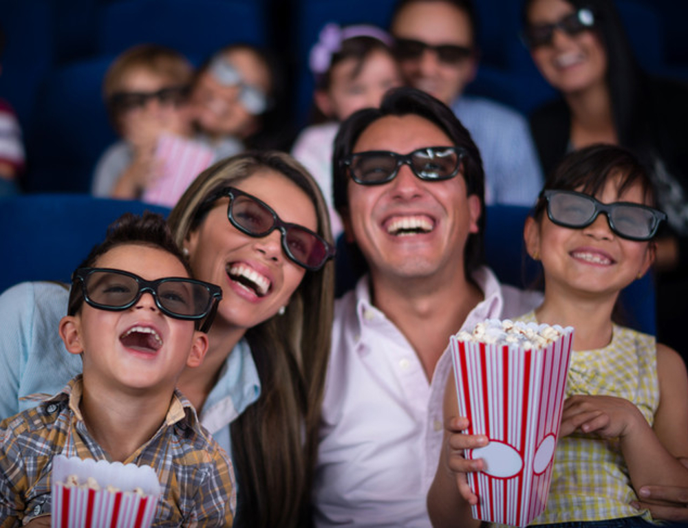 Two parents and two children sit together in a movie theater. All four wear black-rimmed 3-D glasses. They are looking at the screen and smiling widely. Other people are in the background, out of focus.