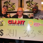 "Three people pose behind an oversized check in the amount of $241,363.30. It has logos for 105.7 ""The X,"" Giant and CMN."