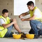 A man in a yellow construction vest sits on the ground against a wall, holding his knee in apparent pain. Another main in a construction vest kneels next to him, preparing to apply a bandage.