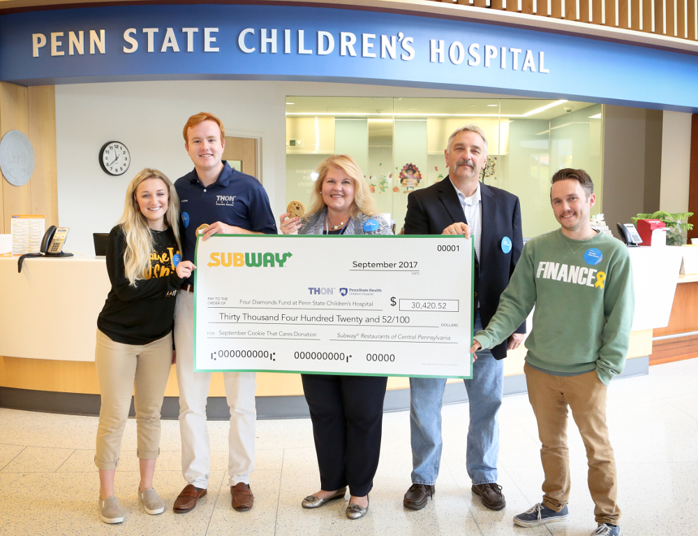 Five people pose for a photo while holding an oversized check in the amount of $30,420.52, from Subway to Four Diamonds at Penn State Children™s Hospital.