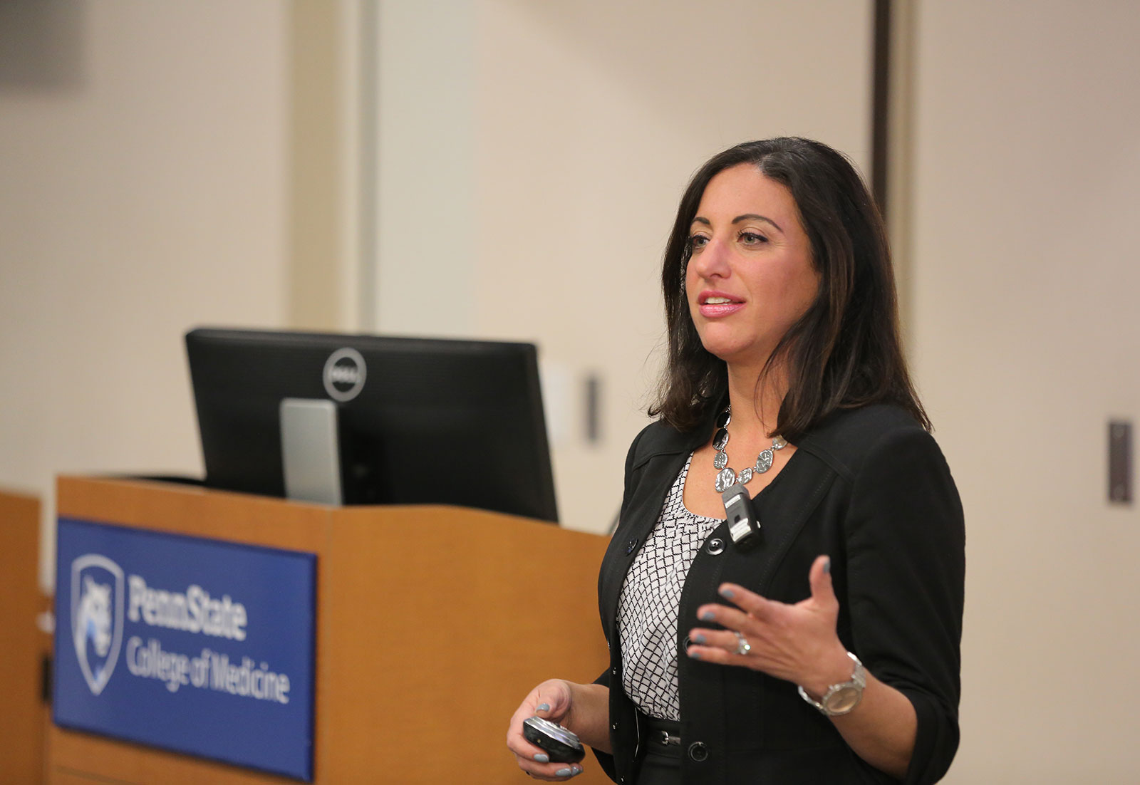 Lori Gavrin, PhD, Director of Business Development for the Platform & Technology Sciences Division at GlaxoSmithKline, delivers the keynote address at the 2017 Innovation Awards ceremony at Penn State College of Medicine, which was held Nov. 28. She is pictured standing in a large conference room, with a podium and computer monitor visible behind her and to the left of the photo. The Penn State College of Medicine logo appears on the podium.