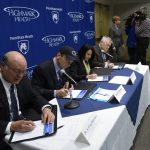 Four people - three men and a woman - wearing business attire sit at a table, each signing a document. A background with the Penn State Health and Highmark Health logos is behind them.