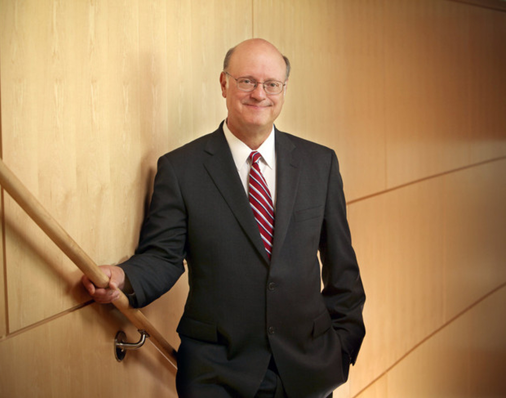 Dr. Craig Hillemeier wears a suit and poses against a wooden wall. His right hand is on the banister, his left hand is in his pocket.