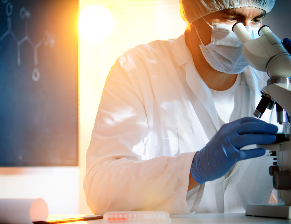 A lab technician in a white coat, blue gloves and a mask and cap looks into a microscope, most of which sits out of the photo to the right. A bright light shines over the individual's shoulder.