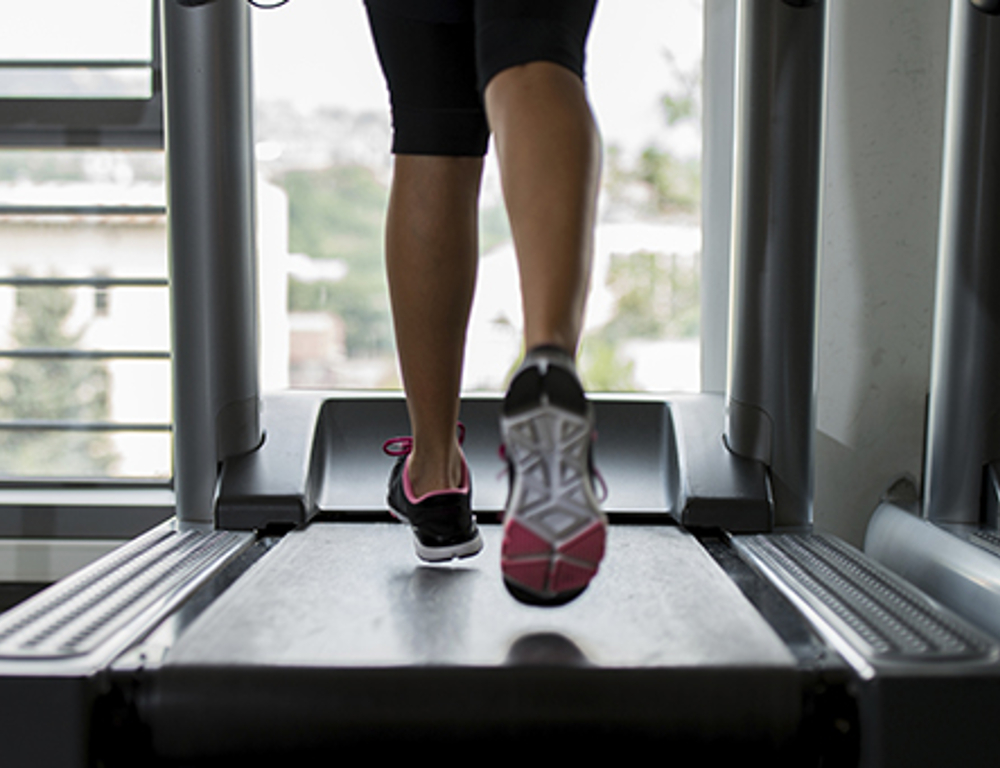 A runner™s legs on a treadmill. The runner is wearing sneakers.