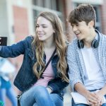 A teenage boy and girl sit together and look into a phone the girl is holding up, apparently posing for a selfie. A brick building with windows is in the background.