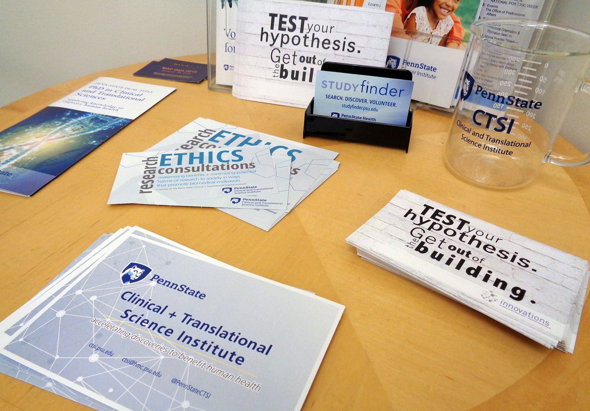 A promotional image for Penn State Clinical and Translational Science Institute shows a number of pamplets, cards and other items advertising CTSI services spread out on a table.