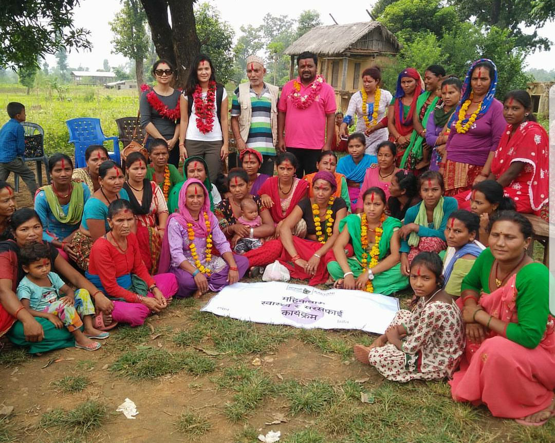 Penn State College of Medicine student Aditi Sharma, standing in the back row, second from left, and wearing a white top, is seen with community members in midwest Nepal. Sharma is pictured with dozens of men, women and children standing and seated in front of her. A small building is visible in the background.