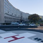 """The Life Lion helipad at Hershey Medical Center is in the foreground, with a large white cross with a red """"H"""" in the middle. The Medical Center's signature Crescent building is in the background."""