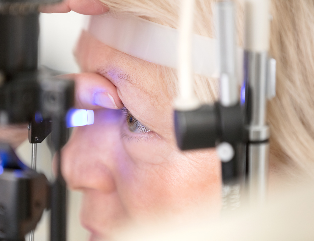 A close-up of a woman with her head placed against a piece of eye exam equipment. The equipment is shining a bright light into her eye, which is being held open by her thumb.
