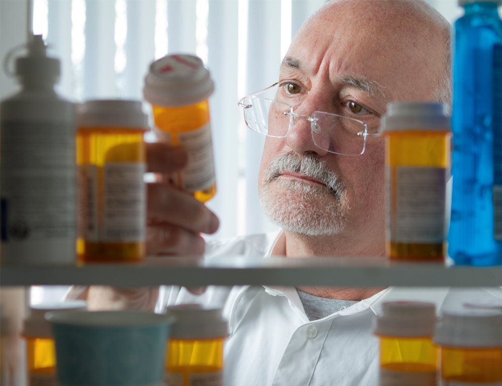 View from inside a medicine cabinet looking out, as a man in a white shirt holds an orange-brown pill bottle and looks at it. Other similar bottles are in the foreground.