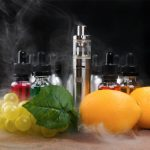 A vaping device sits on a table, surrounded by several dropper bottles with various colors of fluid. In the foreground are grapes, lemons and a green leaf.