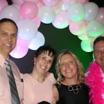 Four people are picutred wearing shades of pink and black at a breast cancer fundraiser party thrown by survivor Kathy, who is pictured third from left. An arch of pink and white balloons is visible behind the people pictured.
