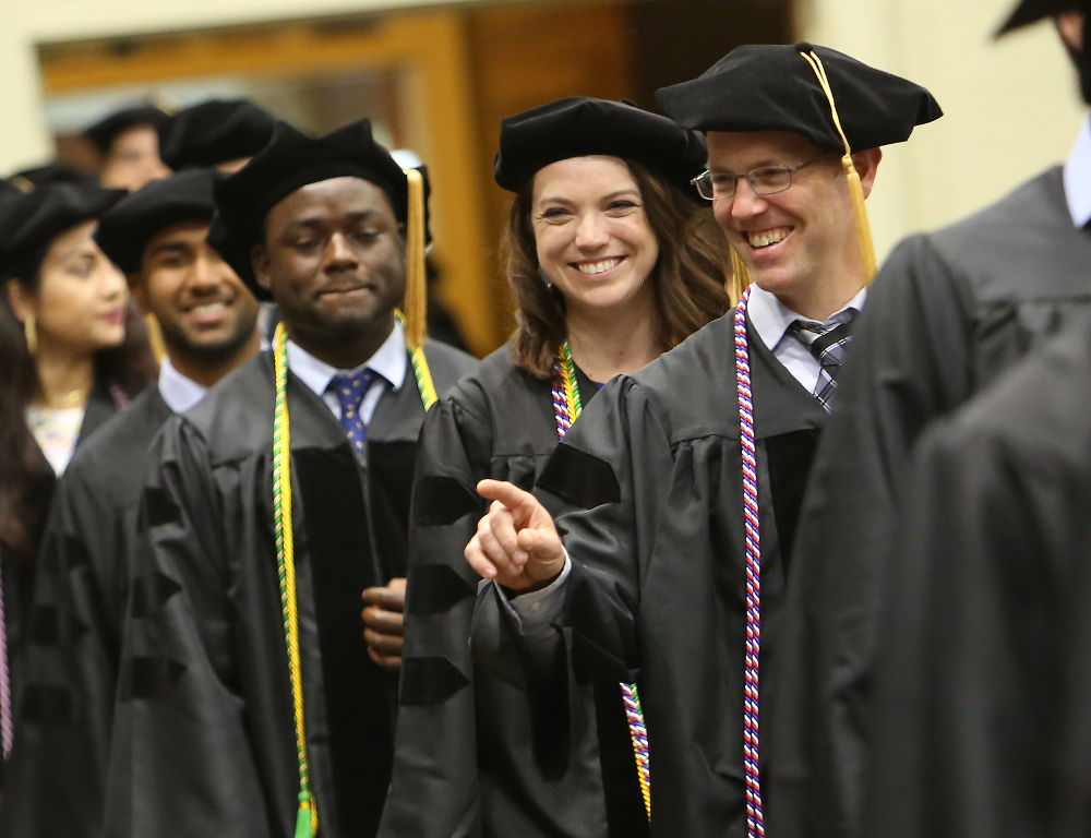 Ben Abney acknowledges someone in the audience as he joins his fellow graduates while entering the 48th commencement for Penn State College of Medicine, held May 20, 2018, at the Hershey Lodge. Abney is pictured smiling and pointing, and a row of other students is visible behind him.