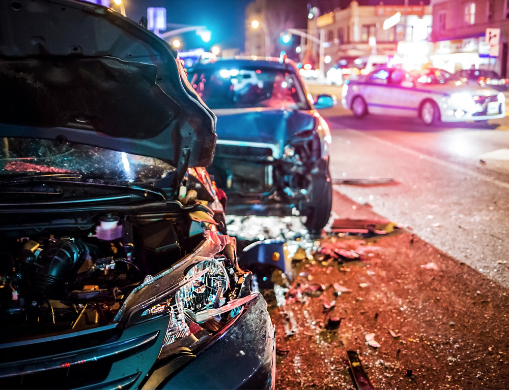 Two cars are parked along the side of a busy city street, each with damage to their front ends from an apparent accident. Bright lights are in the background.