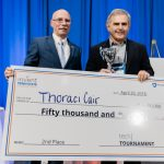 Neil Sharkey, PhD, Vice President for Research, Penn State, left, presents Charles Palmer, MD, and his startup company, ThoraciCair, $50,000 for finishing in second place at the Tech Tournament at the Penn State Venture & IP Conference held in April 2018. The two men are pictured standing next to each other on a stage, both holding a side of a large check made out to ThoraciCair. Palmer is also holding a trophy.