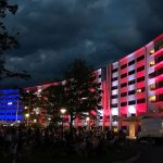 At night, the Hershey Medical Center's signature Crescent building is lit up in red, white and blue lights. Several people are sitting in the foreground.