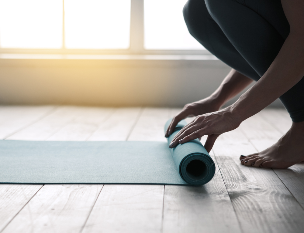 A close-up of a woman™s hands as they roll up a yoga mat, which is on a hardwood floor. Windows are in the background.
