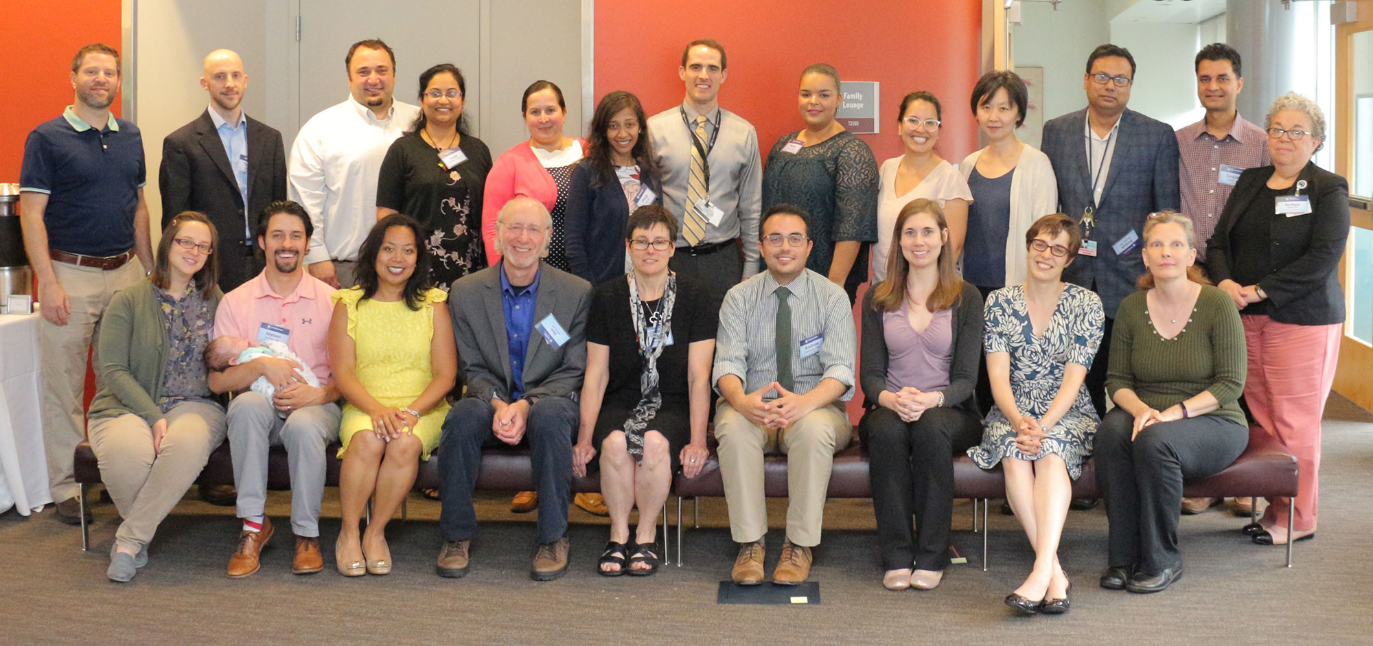 The 2017-2018 participants in Penn State College of Medicine's Junior Faculty Development Program are pictured with program leadership in May 2018. The faculty are pictured sitting and standing in two rows in a large meeting space.