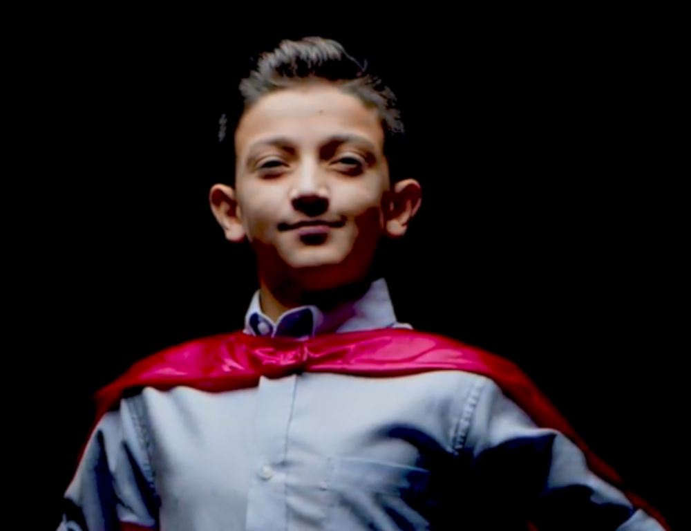 A young boy in a blue shirt and red cape looks into the camera, posing in front of a dark background.