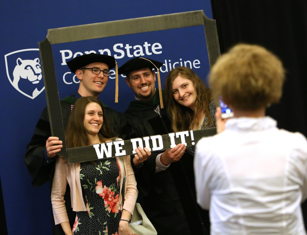 "Four people "" two men and two women "" pose for a photo inside of a hand-held frame with the words We did it! across the bottom. The backdrop has a Penn State College of Medicine logo."