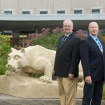 Two men in suits stand back-to-back, slightly off center to the right. A Penn State Nittany Lion statue is at left, and a building is in the background.