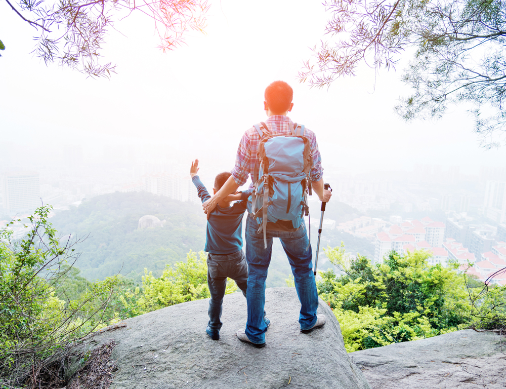 The view from behind as a man and child, dressed in hiking gear, stand on a rock looking off the edge of a mountain. Trees are in the foreground. Buildings and more trees and hills are in the background.