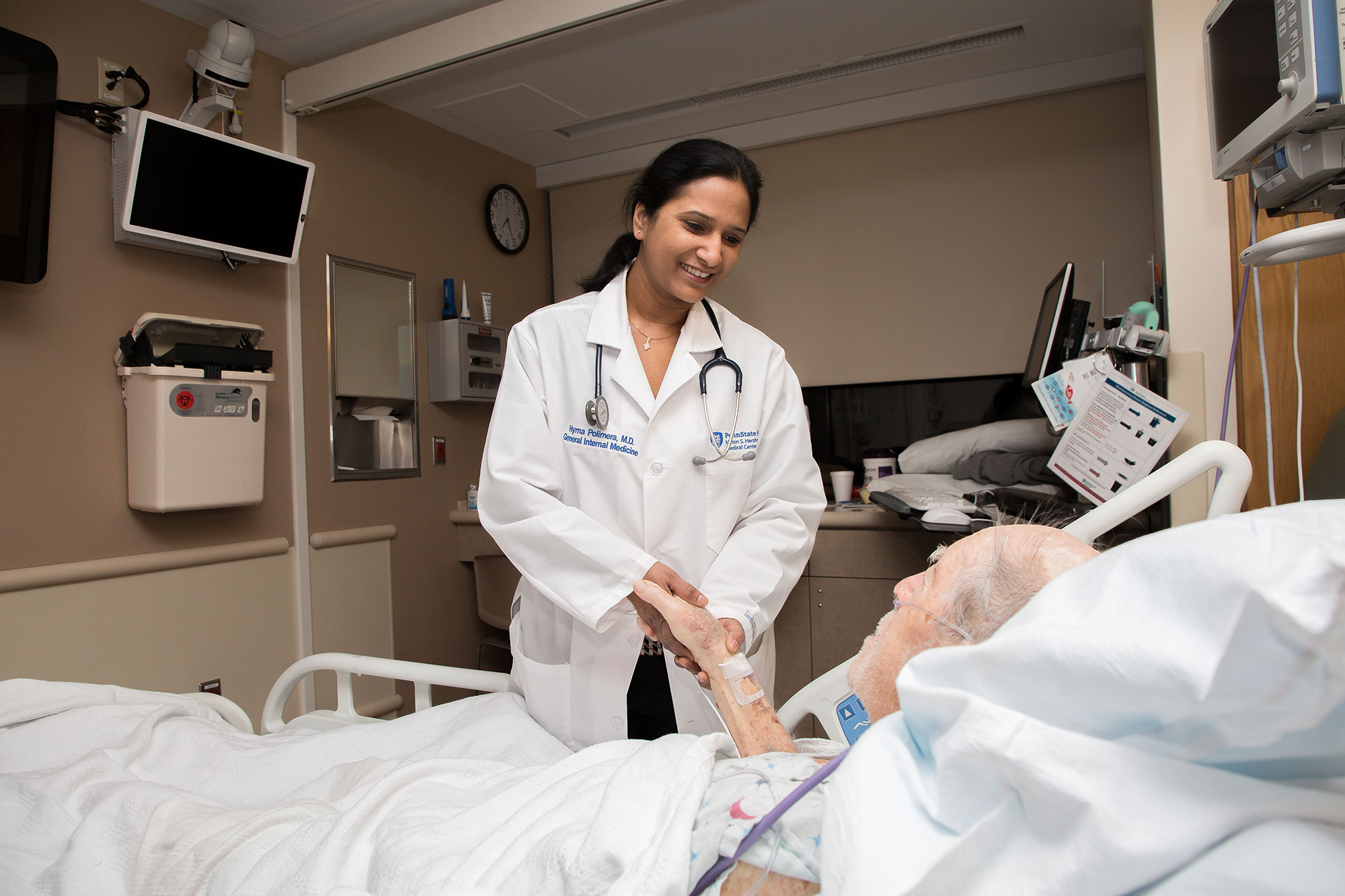 A photo shows Dr. Hyma Polimera at the bedside of a patient at Penn State Health Milton S. Hershey Medical Center.