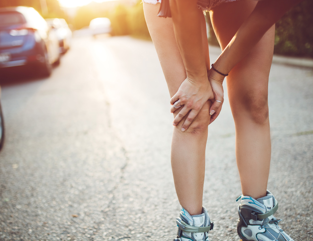 A close-up of a female runner's legs. She grasps her right knee with both hands, as if in pain.