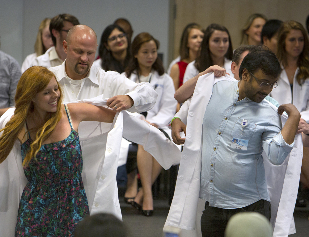 A young woman and a young man in the foreground are each getting help putting on white clinical/lab coats from people standing behind them. In the background, several people wearing white coats are seated, pictured slightly out of focus.