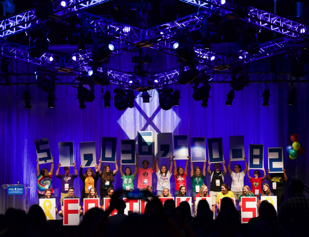 A group of young people stand on a stage holding up individual numbers that spell $7,036,560.82 and letters that spell out FOR THE KIDS.